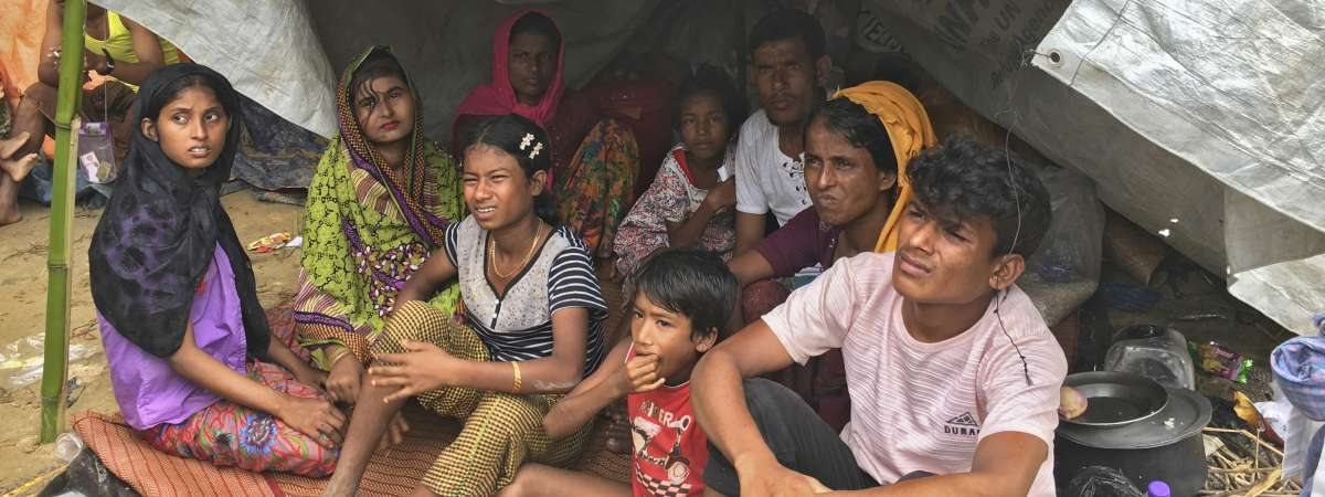 Rohingya crisis 2017 - a family sits on the ground under a makeshift shelter