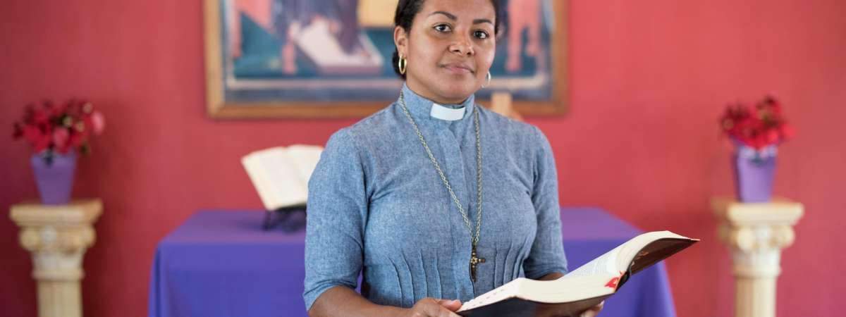 Deacon Elineide Ferreira de Oliveira holding bible and smiling