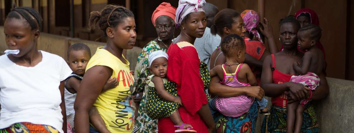 Mothers and children queue for a health clinic in Freetown, Sierra Leone