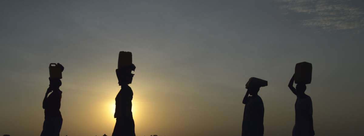 Silhouettes of four displaced women in Sudan