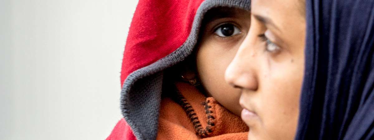 Profile view of a woman in front of a child wearing a hood, in the main image used for our Refugee Crisis Appeal