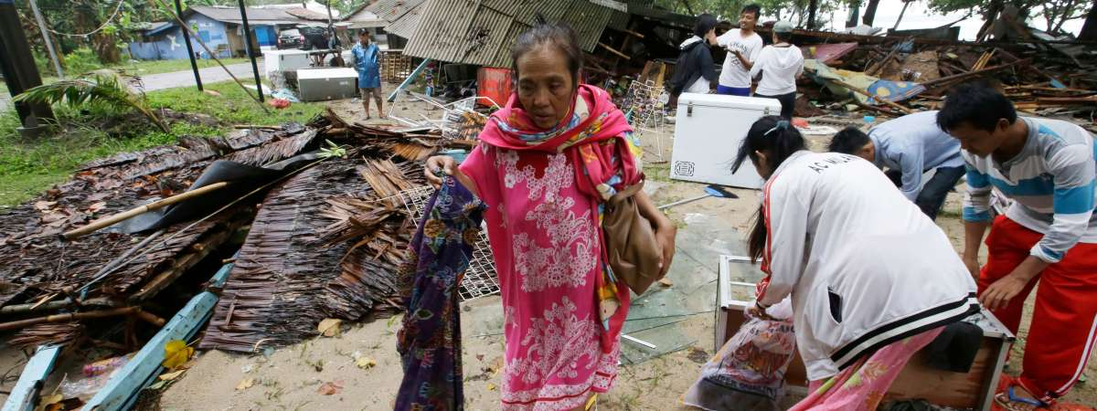 Woman walking amongst debris Indonesia tsunami