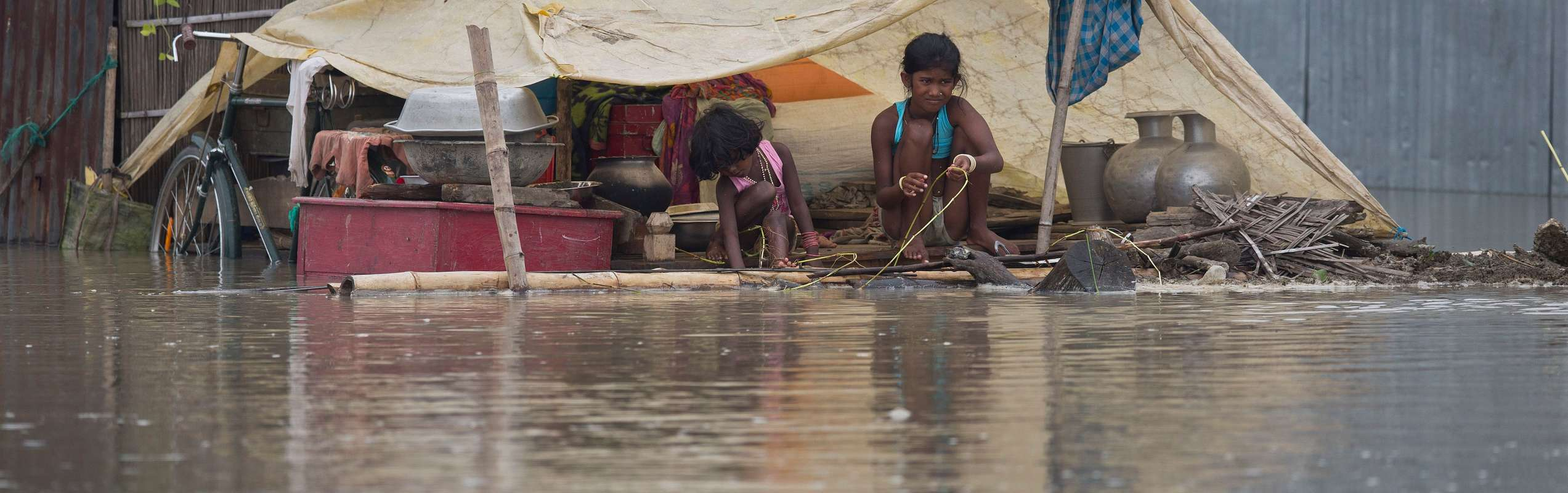 Girls surrounded by floodwater shelter under tarpaulin during India floods