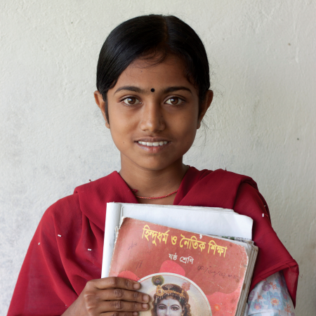 A young girl with books in her arms.