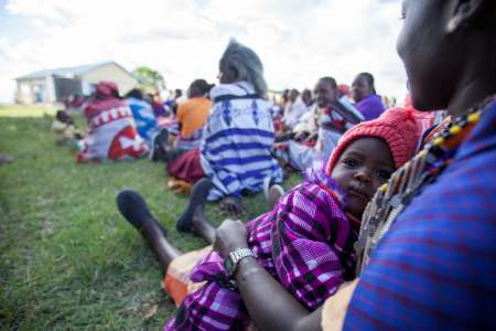 A baby is looking at the camera whilst lying on a woman's lap. The woman is sitting on the grass in a gathering of other women in Narok County, Kenya.