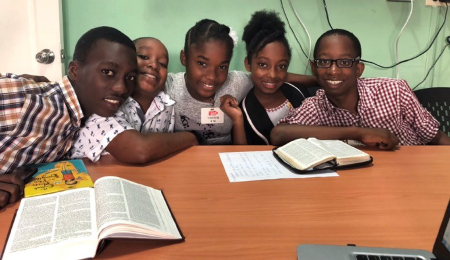 Five youth in Haiti sit around a table with two bibles as part of the Haiti-Crewe Connection from Just Scripture