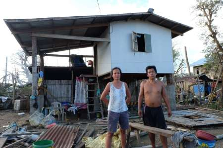 Florentino and Mary Rose Leones stand in front their typhoon-damaged house in the Philippines.