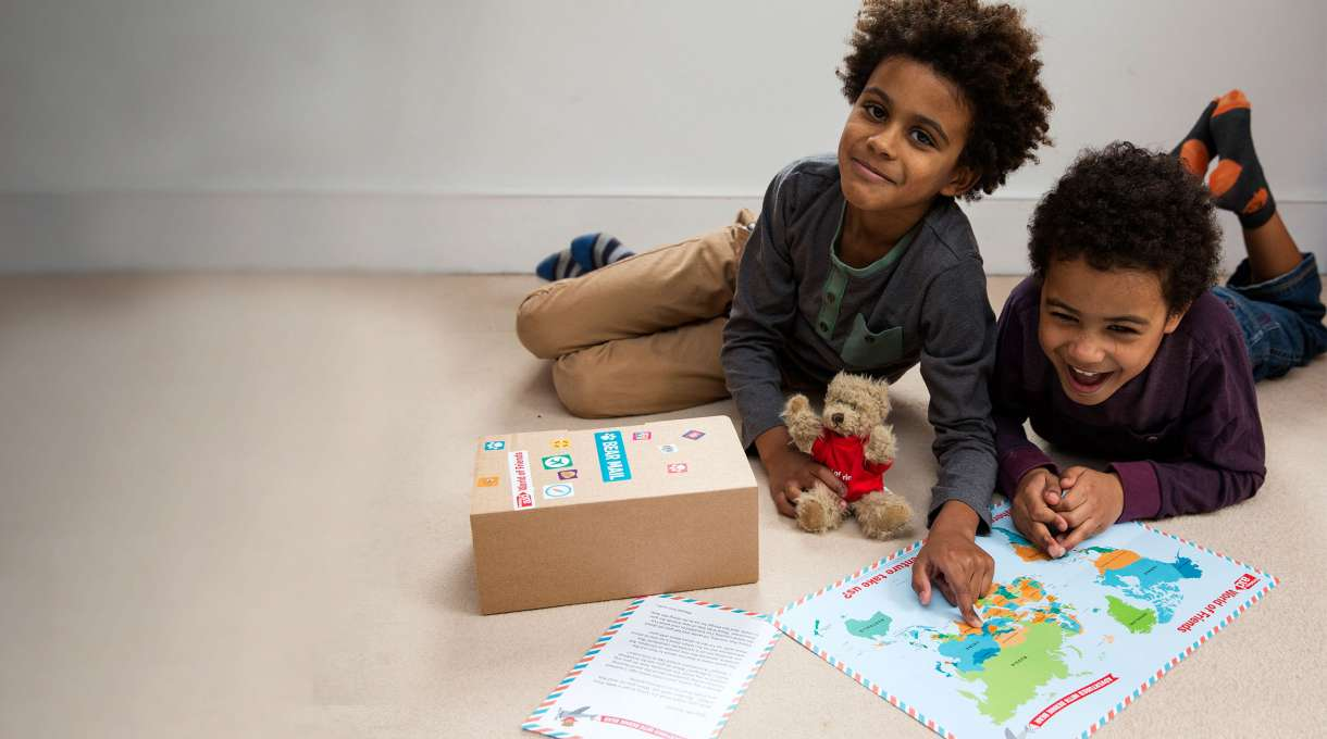 Two children play with the contents of the World of Friends box