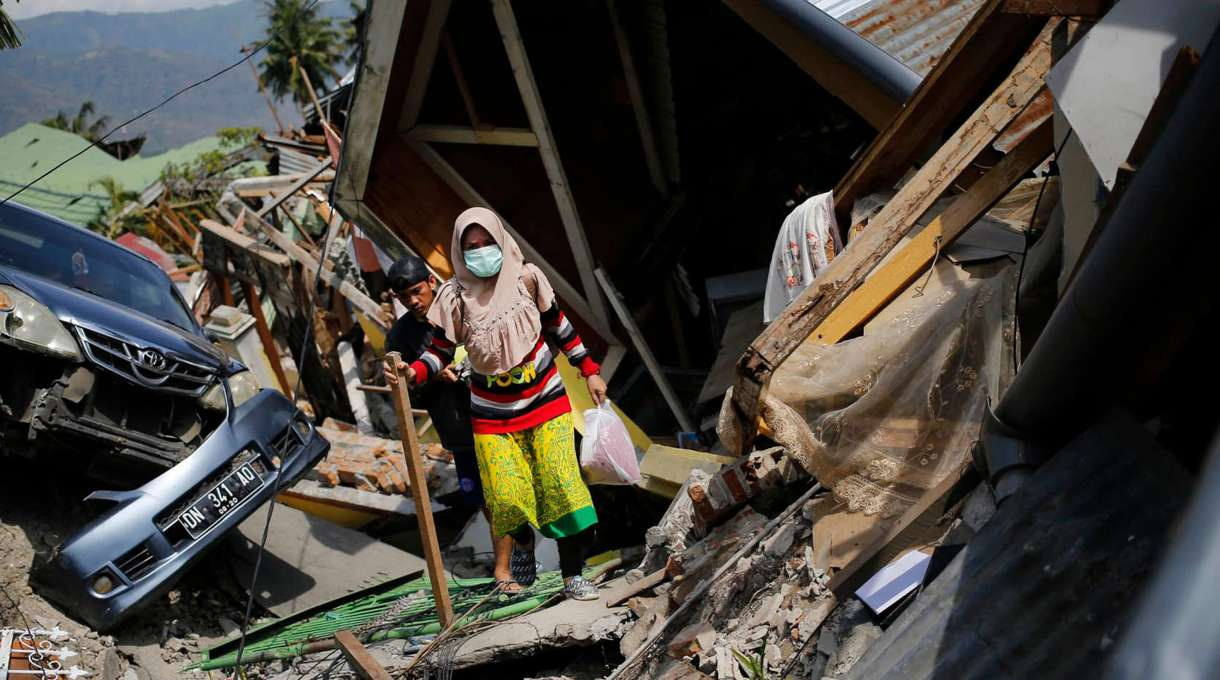 A woman makes her way through the rubble of houses after the earthquake and tsunami in Indonesia