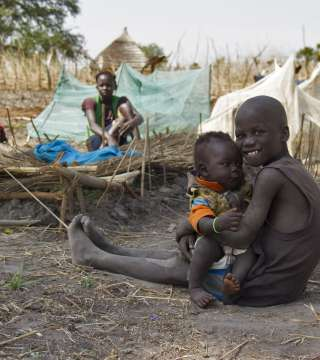 Two young children sitting on the ground, South Sudan