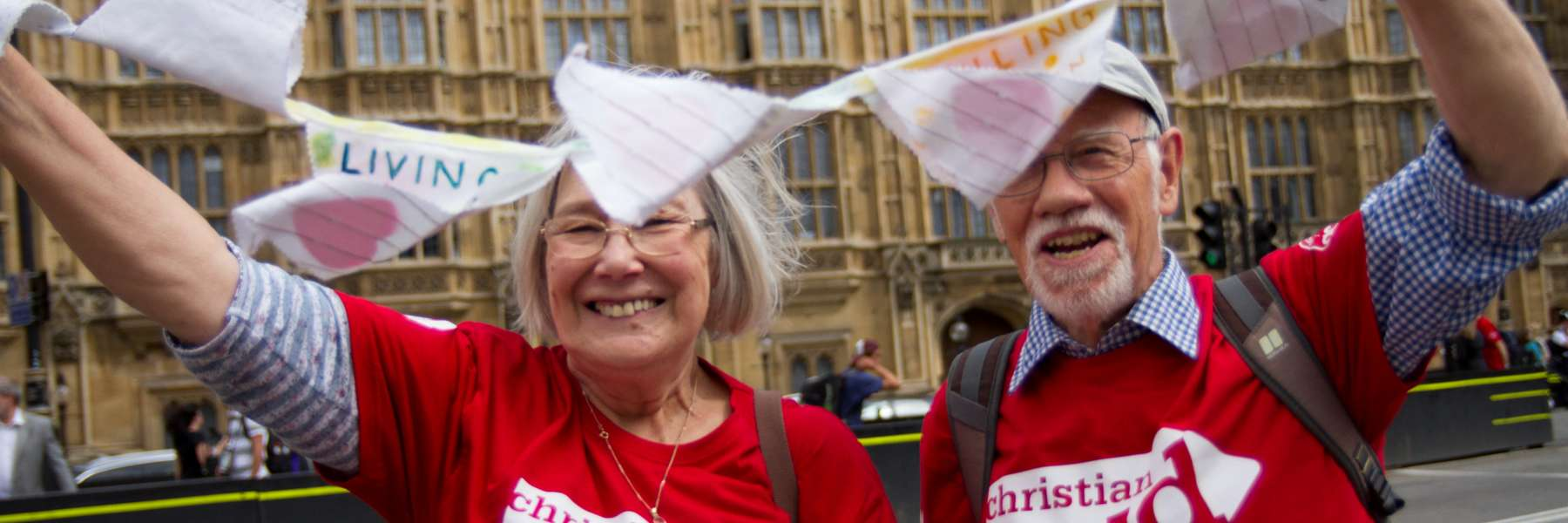 Two supporters wave bunting outside Parliament