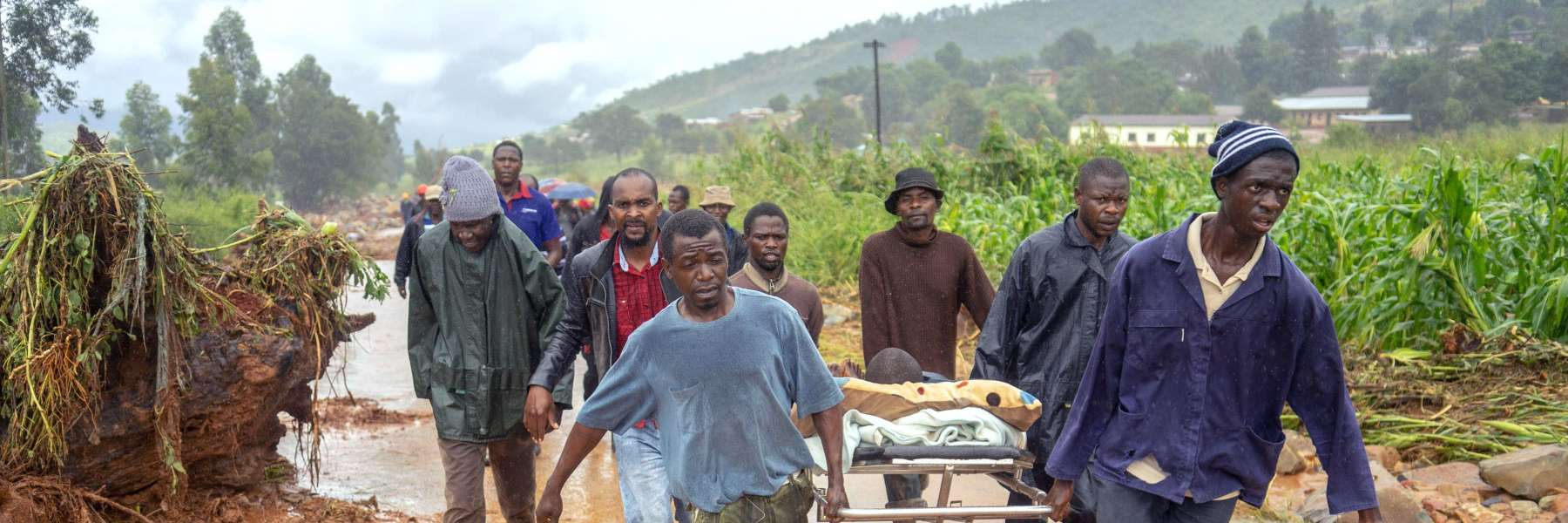Group carrying injured person on stretcher following Cyclone Idai
