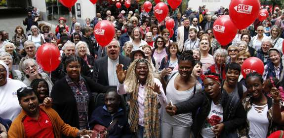 Large group of smiling supporters holding red Christian Aid balloons