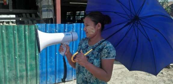 Woman on loudspeaker to spread the health message on coronavirus in Myanmar