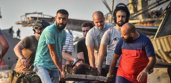 Group of men carry injured man on a stretcher away from Beirut explosion