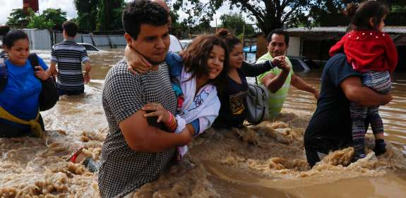 Family in Nicaragua wade through flood water after Hurricane Iota