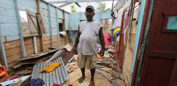 Man stands in his ruined home after Hurricane Iota