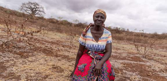 Rose Katanu Jonathan sitting on the dry land caused by extreme drought in Dili Village, Kitui.