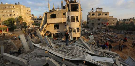 People in Gaza explore the rubble after bombings