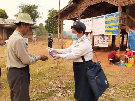 Volunteer providing hand sanitiser to elderly man