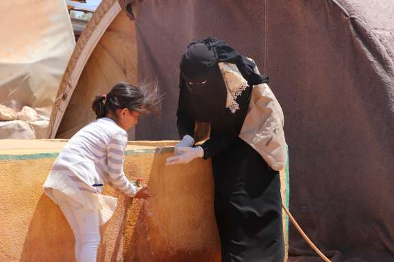 Volunteer training young girl in hand washing