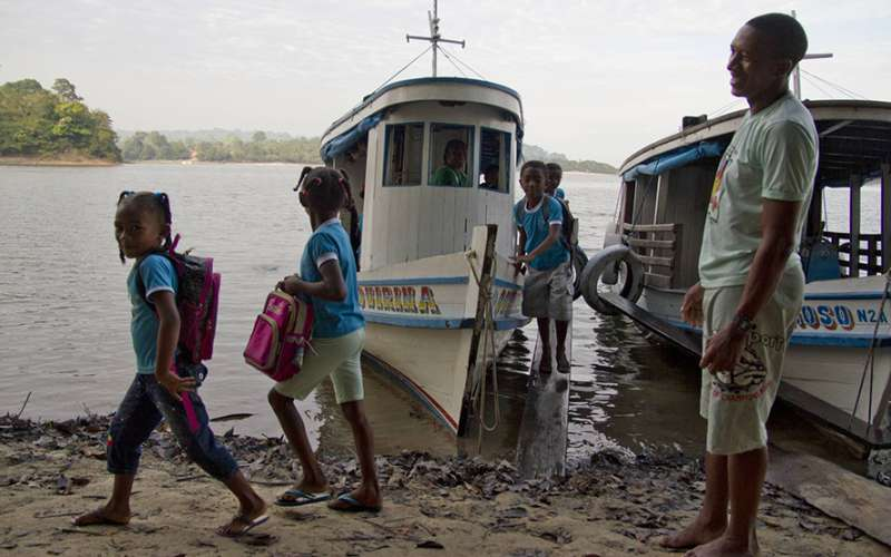 Brazilian children going to school by boat