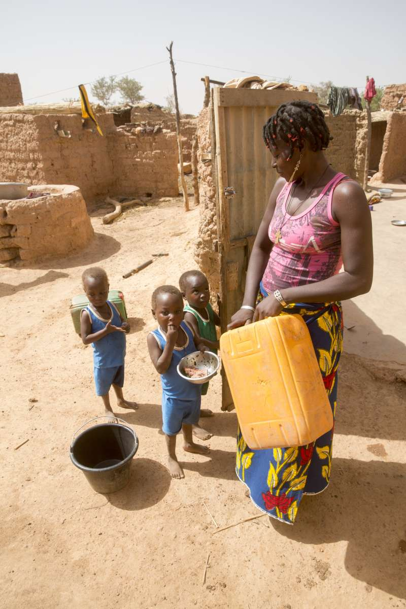 Salamata holds a jerry can and her children stand in front of her, eating from bowls