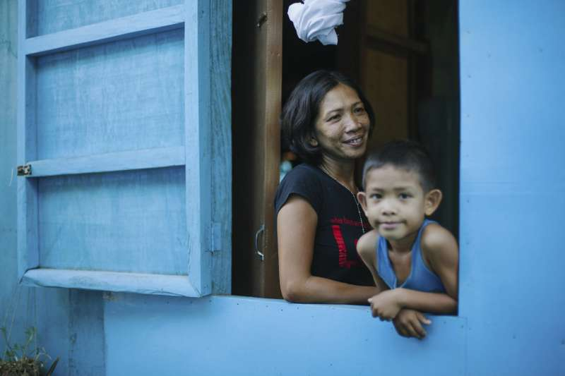 Sussett Enolva and son look out of a window from their new, blue house in the Philippines