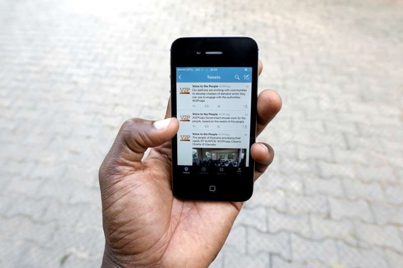 Hand holding mobile displaying tweets from Voice to the People.