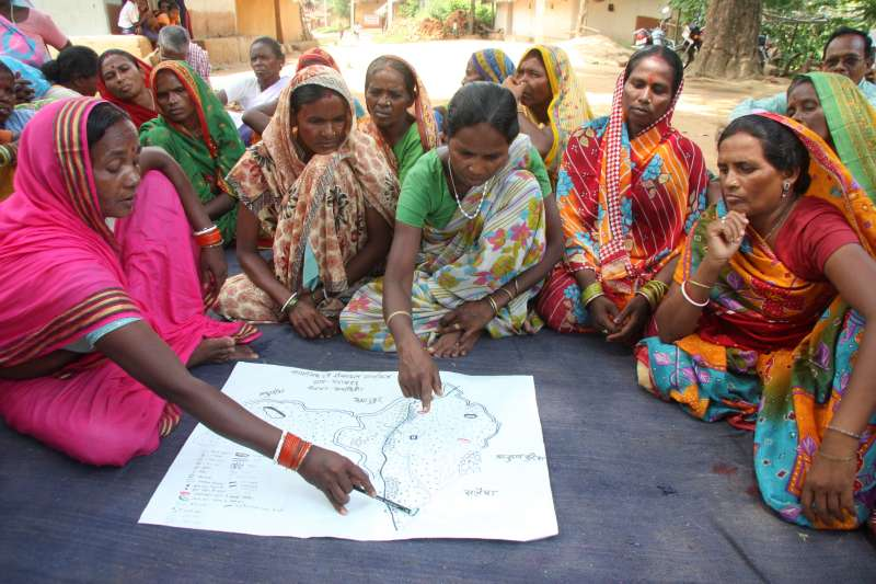 Women in brightly coloured saris pore over map in Jharkhand, India.