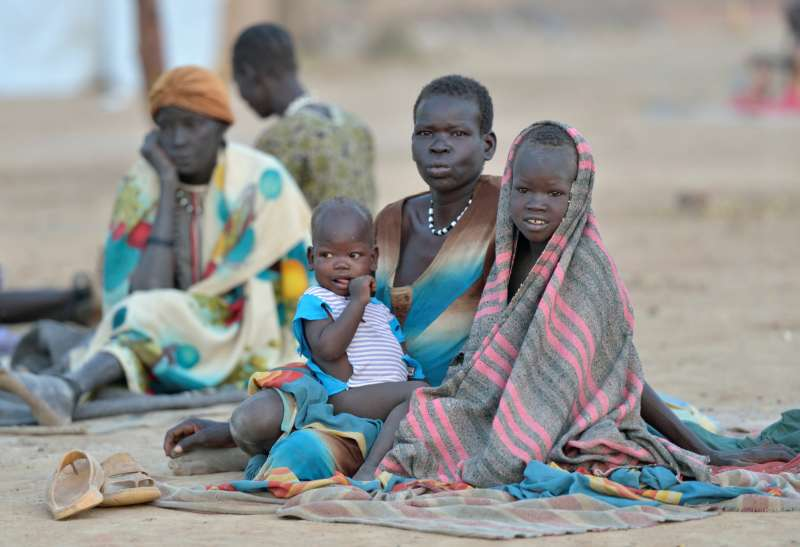 A woman and 2 young children sit on the floor wrapped in blankets at a displaced persons camp in South Sudan