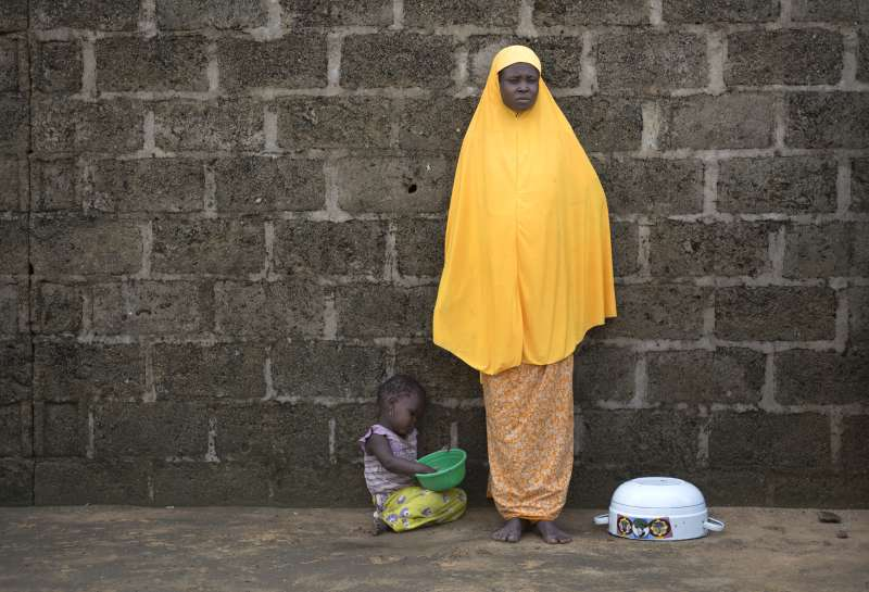 Women with yellow scarf stands against wall with small child