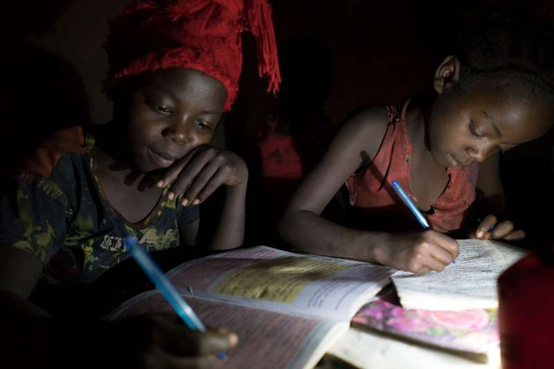 Agar and sibling reading by solar lamp