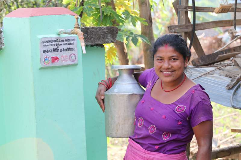Leela Shrestha with the water tap stands constructed by Christian Aid and FOCUS Nepal