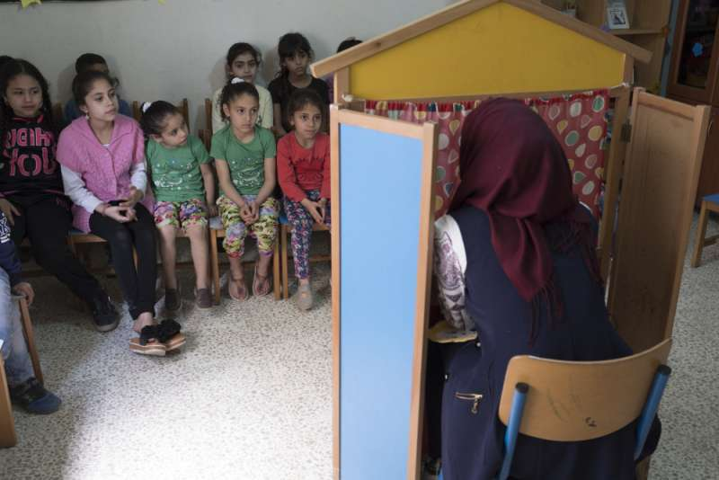 Fedaa Bader, 23, performs a puppet show for children at the centre to teach them about the importance of personal hygiene, such as brushing their teeth and washing their hands.