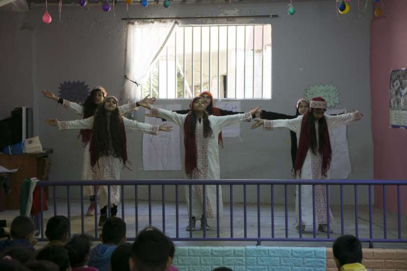 A group of young Palestinian girls perform a traditional dance at a community event hosted at Association Najdeh's kindergarten building.