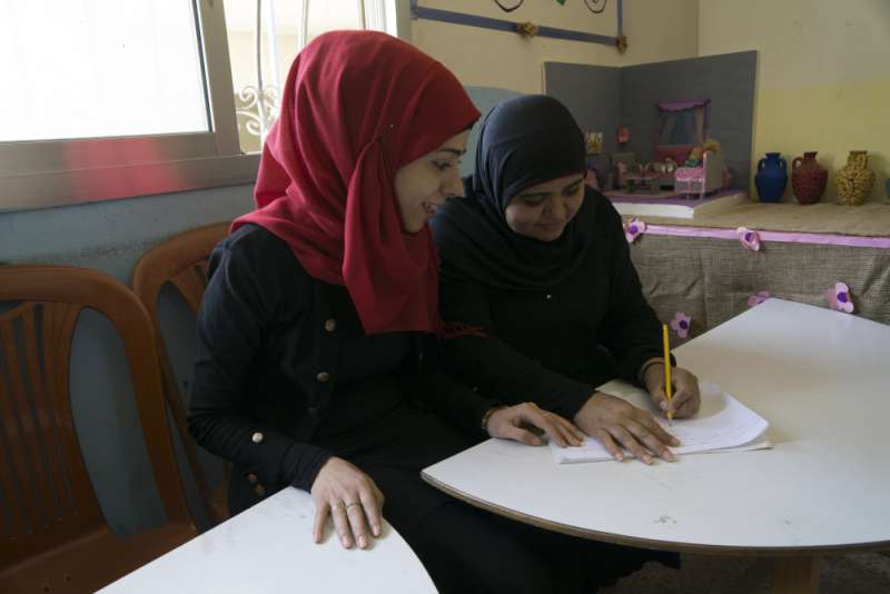 Malaki Khwailed (right) has recently learned to read and write after attending adult literacy classes at the centre.