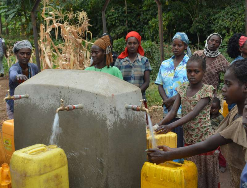 Children filling jerry-cans with clean water