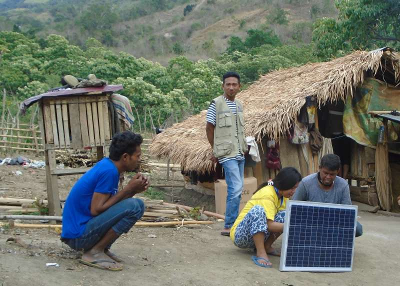 Villagers examine a solar panel in Kawatune, Central Sulawesi