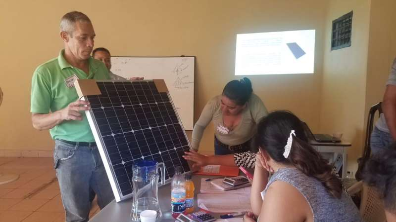 Women take part in a technical workshop on solar panels.