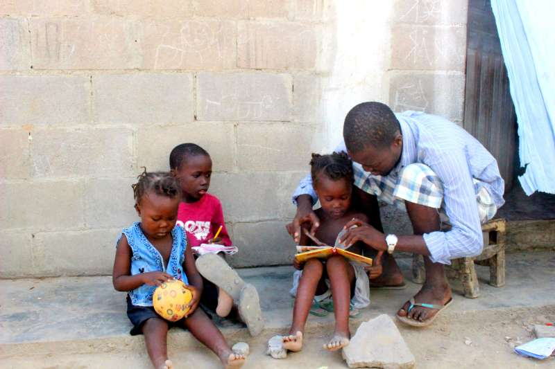 Evaristo looking at books with his children in Angola
