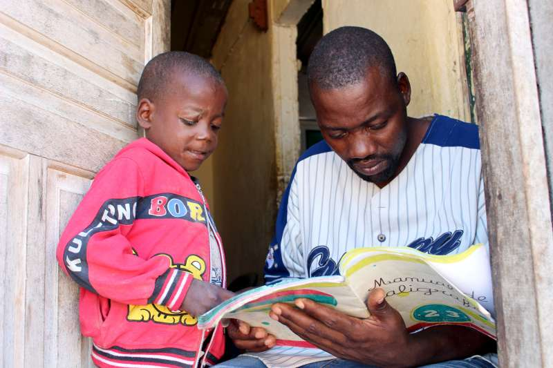 Rafael and son Manuel reading in a doorway, in '16 June' community in Angola