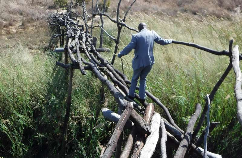 Pastor Ezekias from IECA crosses the rickety bridge over the river near Kapalandanda, Mavinga