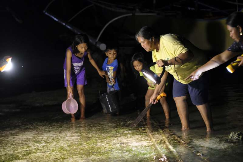 Virginia and grandchildren fishing at night by solar light
