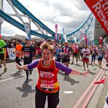 Eileen, a Christian Aid London Marathon runner runs across Tower Bridge in London
