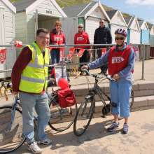 Christian Aid supporters in front of beach huts on Bournemouth beach