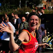 A female Christian Aid runner taking part in the Great North Run 2015 waves at the camera