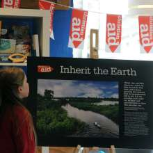 A girl, with her back to the camera, stands in front of a poster from Christian Aid's Inherit the Earth photo exhibition