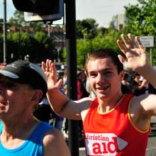 A runner in a Christian Aid vest waves at the camera