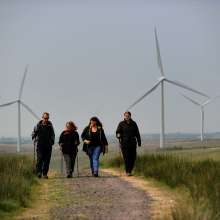 Four people walking along a country path with wind turbines in the background